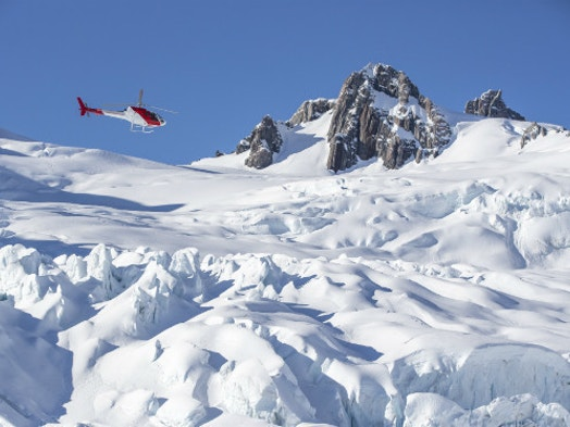 Helicopter flying to Mount Cook over snow capped mountains
