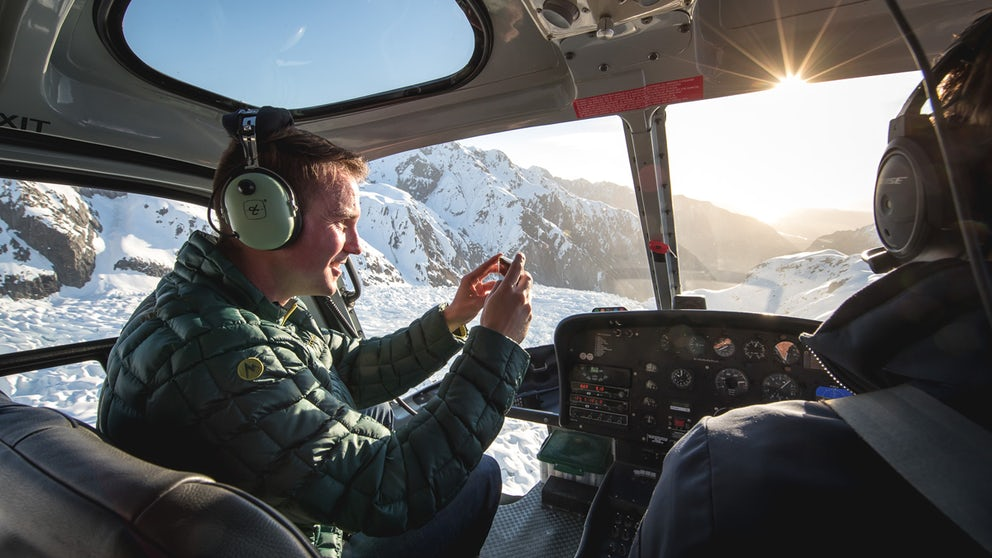 Passenger Taking Photos Of A Glacier From The Front Seat Of A Helicopter