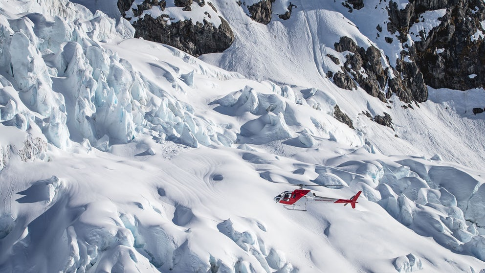 Helicopter Flying Over Glacial Ice Structures