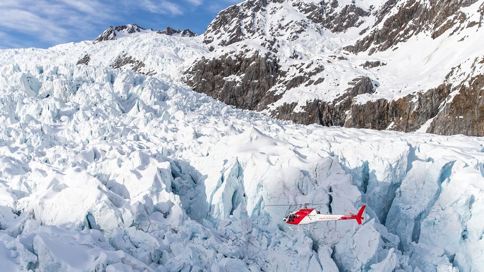 Helicopter Flying Close To Glacial Features