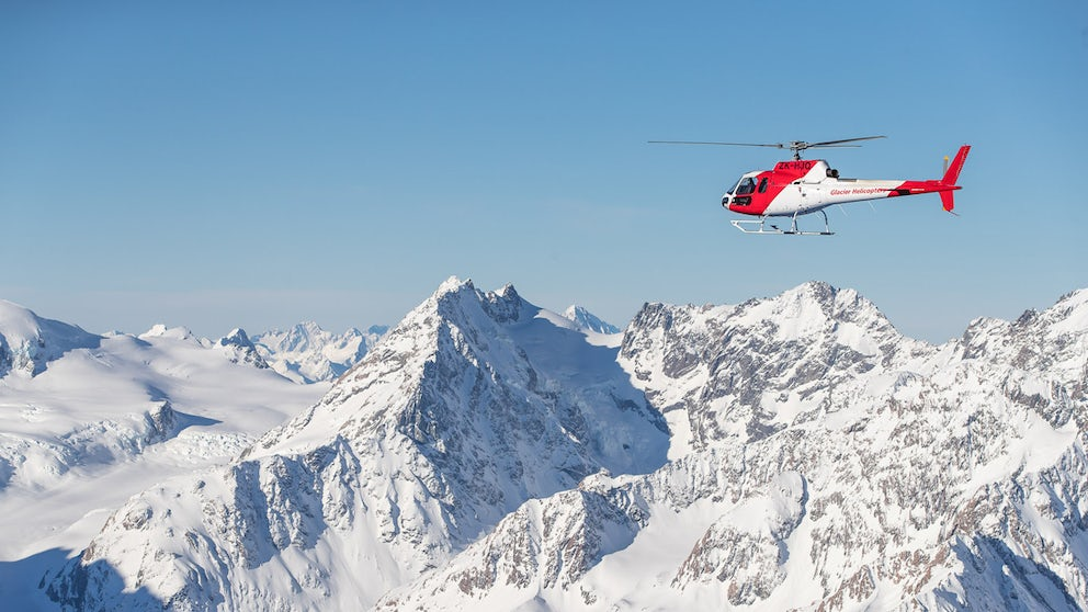 Helicopter Flying Next To Snow Covered Mountains