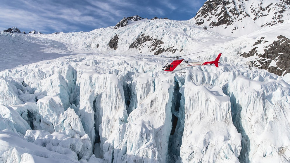 Helicopter Hovering Above Glacial Crevasses