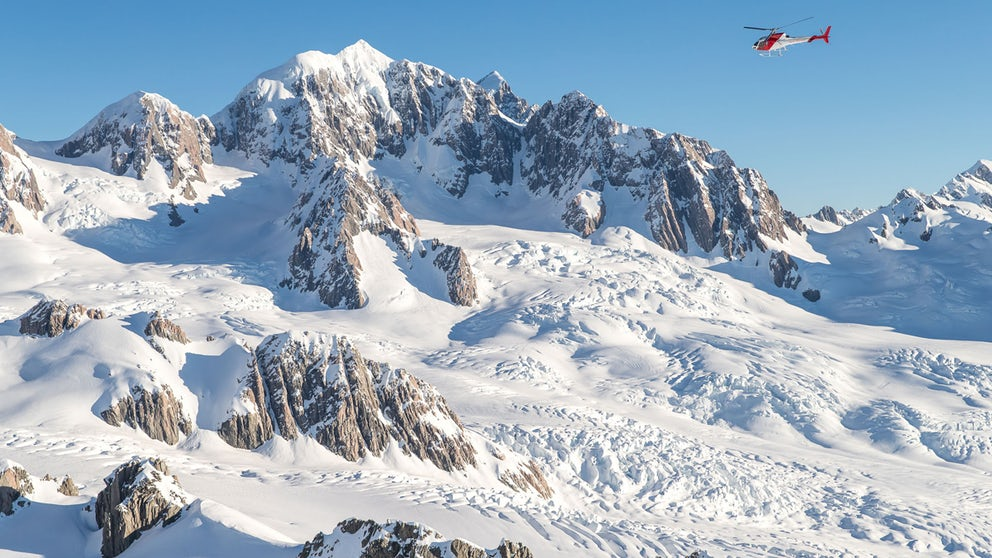 Helicopter Hovering High Above Glacier With Towering Mountains In The Background