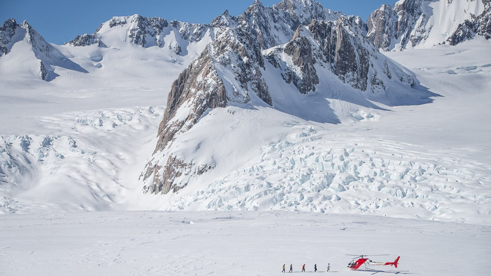 People Walking Towards Their Helicopter On A Glacier