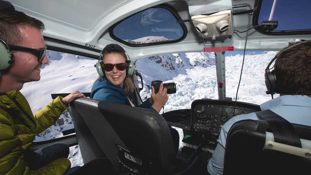 Two Friends Smiling & Taking Photos As They Fly Over Ice Structures In A Helicopter