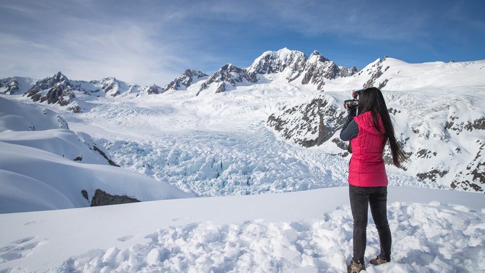 Woman Taking Photos Whilst Standing On A Glacier