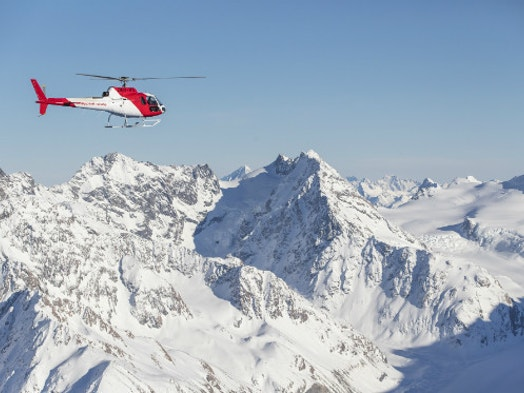 Helicopter Flying Next To Snow Capped Mountains