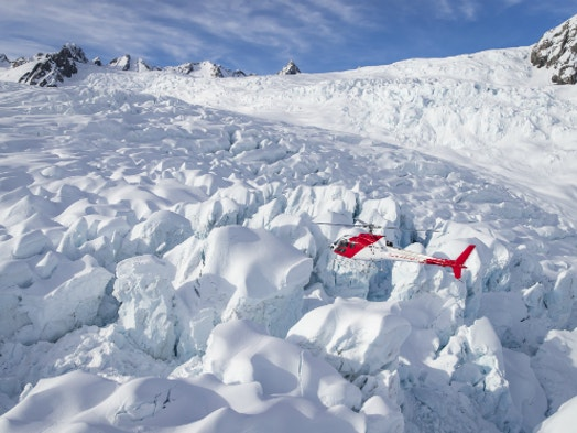 Helicopter Hovering Over Glacial Features