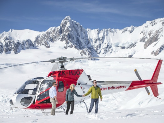 Pilot Helping Two People Out Of A Helicopter For A Snow Landing